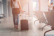 Mujer con maleta de cabina en aeropuerto